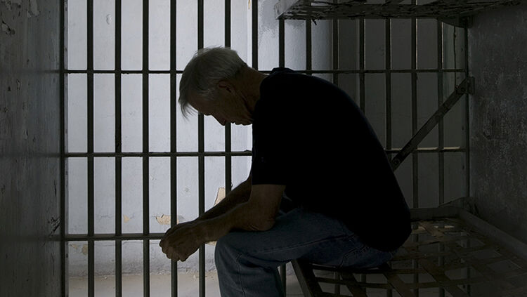 Sad and lonely older man in a prison cell