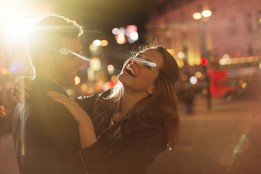 Couple hugging on city street at night