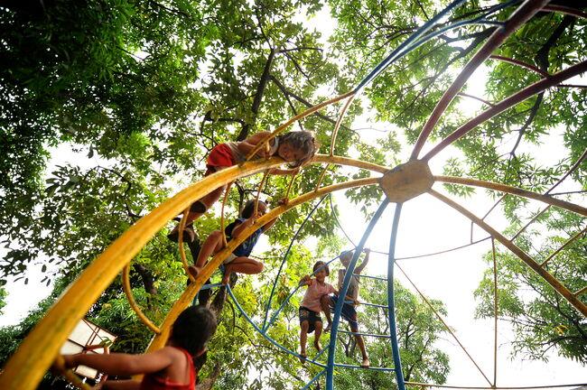 Children climb on playground equipment i