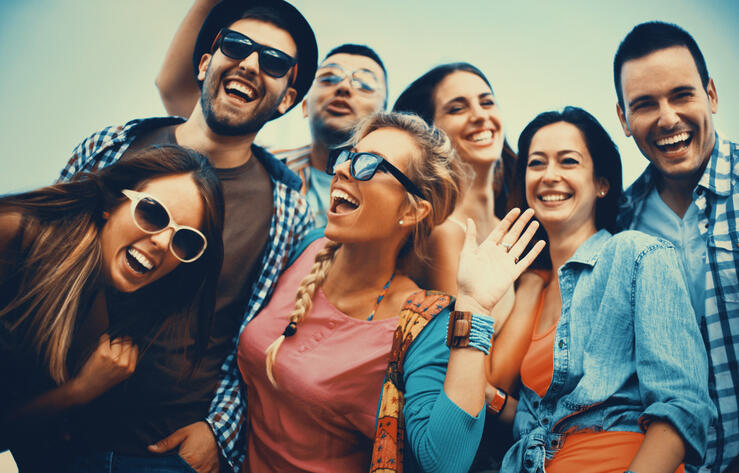 Closeup low angle view of group of mid 20's people having fun and laughing.Standing side by side, there are three guys and four girls.All wearing casual clothes and facing camera.Some wearing sunglasses.