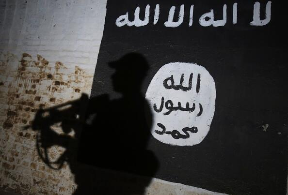 A member of the Iraqi forces walks past a mural bearing the logo of the Islamic State (IS) group in a tunnel that was used as a training centre by the jihadists, on March 1, 2017, in the village of Albu Sayf, on the southern outskirts of Mosul. Iraqi forces launched a major push on February 19 to recapture the west of Mosul from the Islamic State jihadist group, retaking the airport and then advancing north. / AFP / AHMAD AL-RUBAYE        (Photo credit should read AHMAD AL-RUBAYE/AFP/Getty Images)