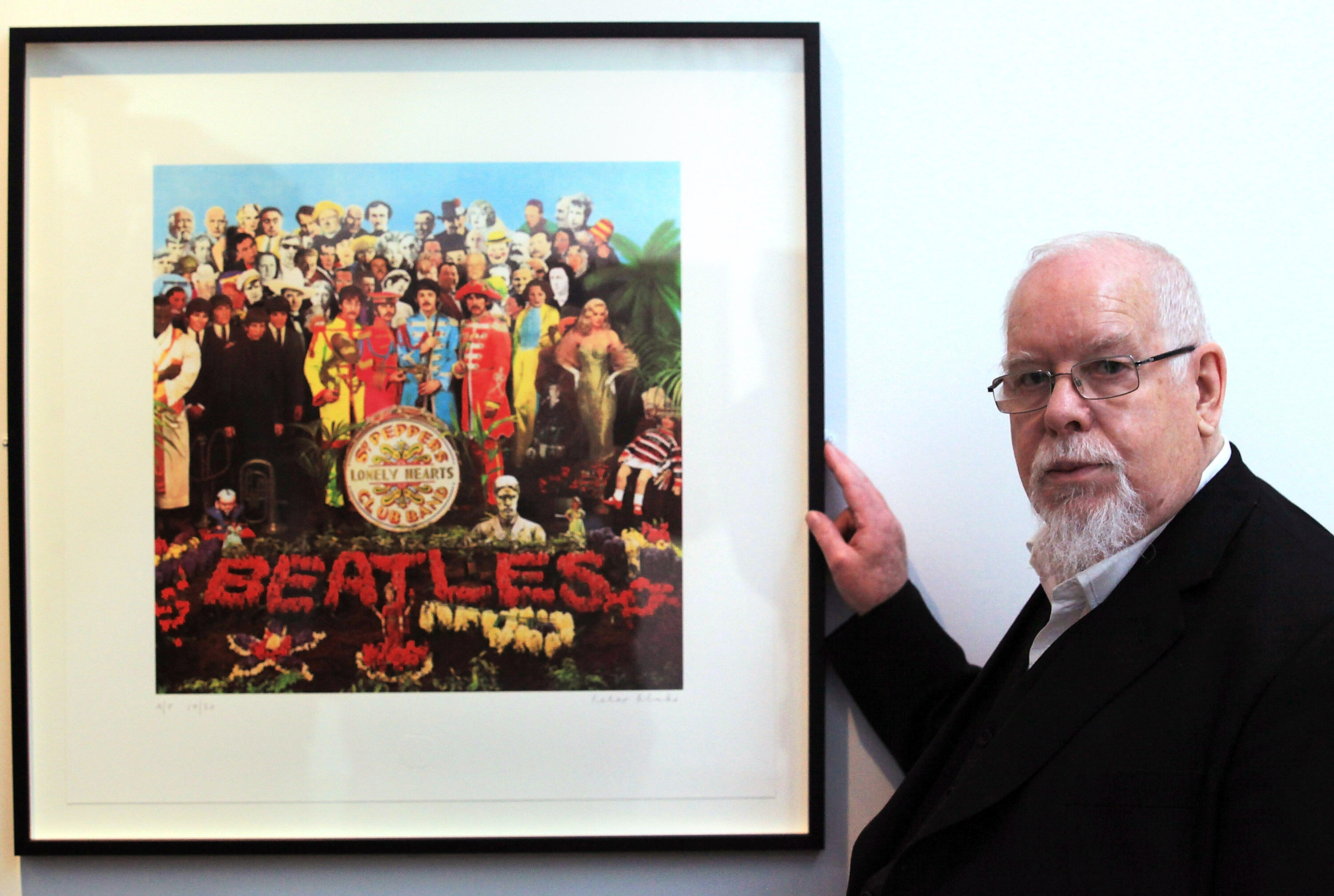 BATH, ENGLAND - MAY 12:  Artist Peter Blake poses for a photograph besides a copy of The Beatles Sgt Pepper LP album cover that he designed in 1967 as he reopens the Holburne Museum on May 12, 2011 in Bath, England. The new museum's first exhibition  - wh