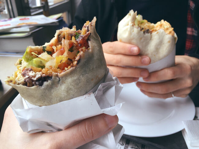 Cropped Hands Holding Burritos At Restaurant