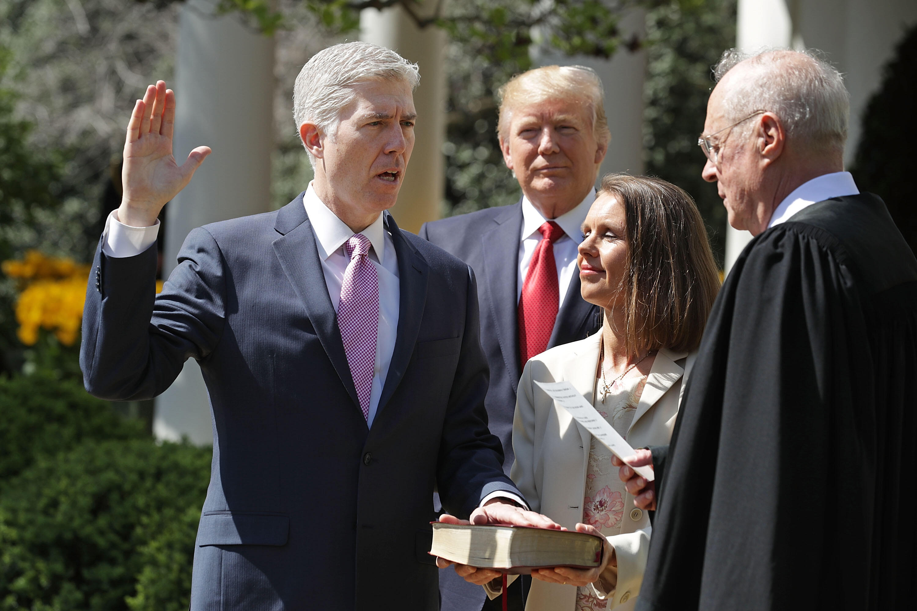 WASHINGTON, DC - APRIL 10:  U.S. Supreme Court Associate Justice Anthony Kennedy (R) administers the judicial oath to Judge Neil Gorsuch (L) as his wife Marie Louise Gorshuch holds a bible and President Donald Trump looks on during a ceremony in the Rose