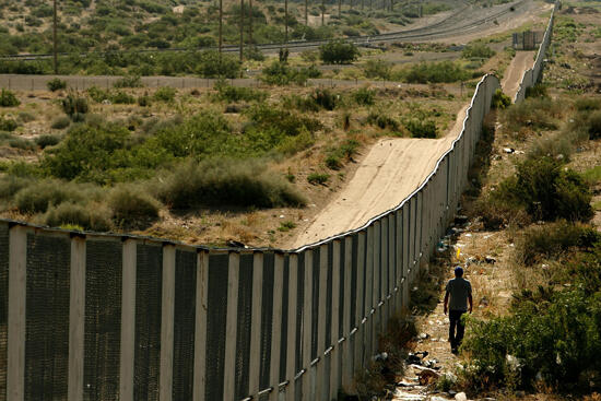 CIUDAD JUAREZ, CHIHUAHUA - JUNE 29:  A man walks along the border fence between the U.S. and Mexico on June 29, 2007 in the Anapra area of Ciudad Juarez, Mexico. This area is a popular crossing spot for immigrants to ilegally cross into the United States