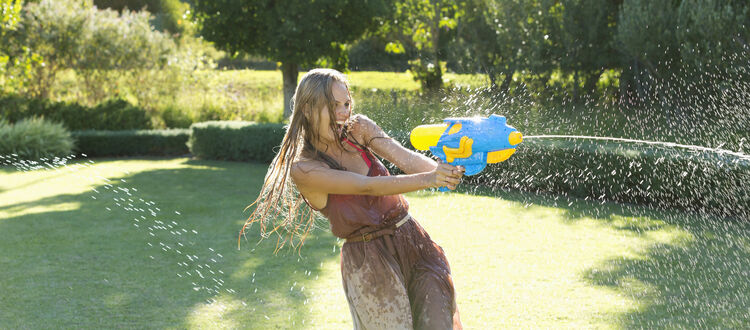 Girl playing with water gun in backyard