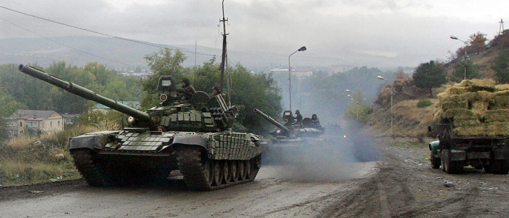 Russian tanks drive along a road outside