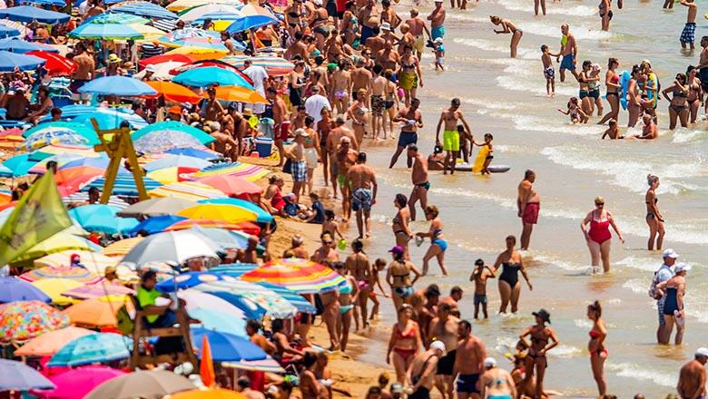 BENIDORM, SPAIN - JULY 22:  People sunbathe at Levante Beach on July 22, 2015 in Benidorm, Spain. Spain has set a new record for visitors, with 29.2 million visitors in June, 4.2% more than the same period in 2014. Spain is also expected to be the main de