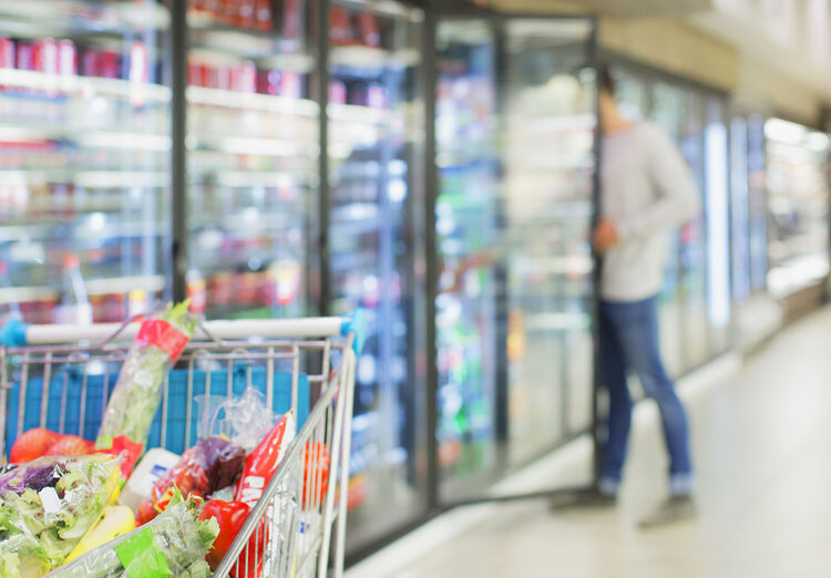 Defocussed view of man shopping in grocery store