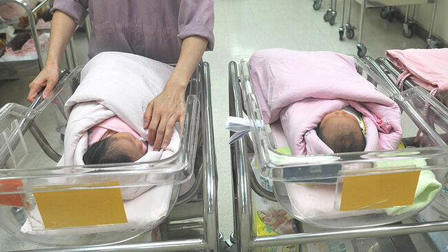 A nurse inspects a newborn baby at a nur