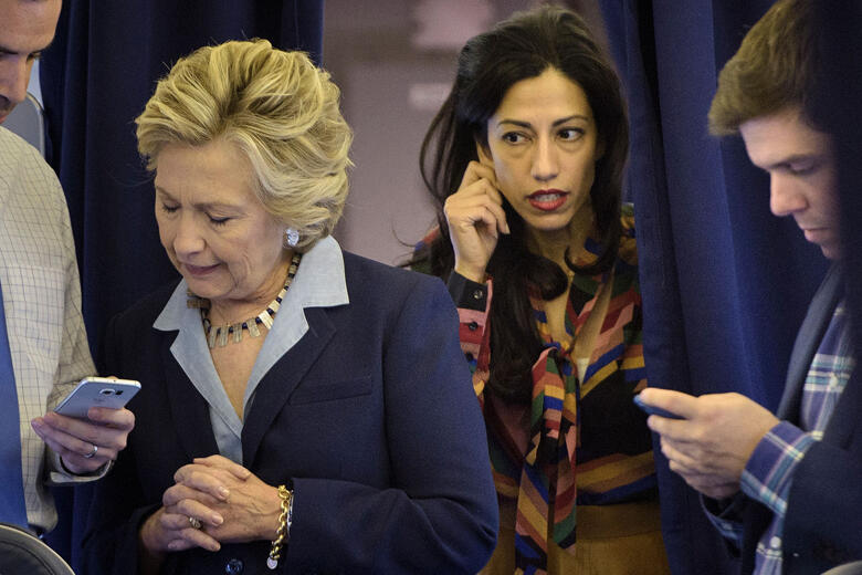 Democratic presidential nominee Hillary Clinton (2L) looks at national press secretary Brian Fallon's (L) smart phone while on her plane with aid Huma Abedin (2R) and traveling press secretary Nick Merrill (R) at Westchester County Airport October 3, 2016