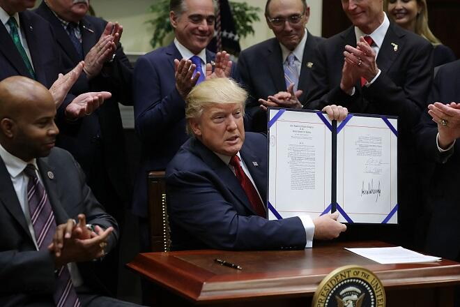 WASHINGTON, DC - APRIL 19:  U.S. President Donald Trump holds up the Veterans Choice Program And Improvement Act while being applauded by representatives of veterans' organizations, politicians and members of his administration, including Veterans Affairs