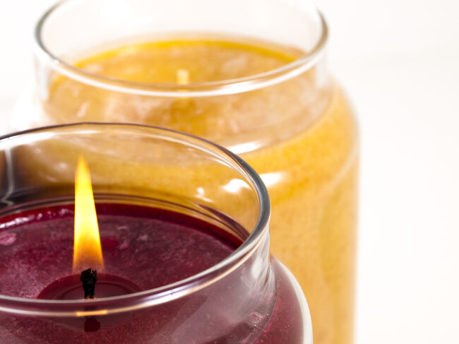 A maroon candle burning next to an orange candle not burning