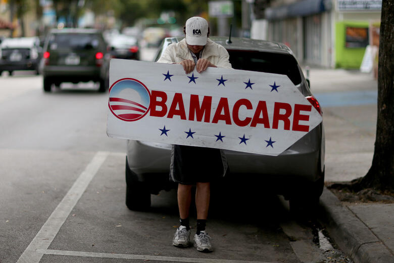 MIAMI, FL - FEBRUARY 05:  Pedro Rojas holds a sign directing people to an insurance company where they can sign up for the Affordable Care Act, also known as Obamacare, before the February 15th deadline on February 5, 2015 in Miami, Florida. Numbers relea
