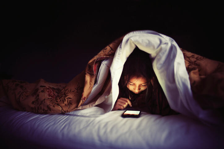 Girl using smartphone under bed covers.