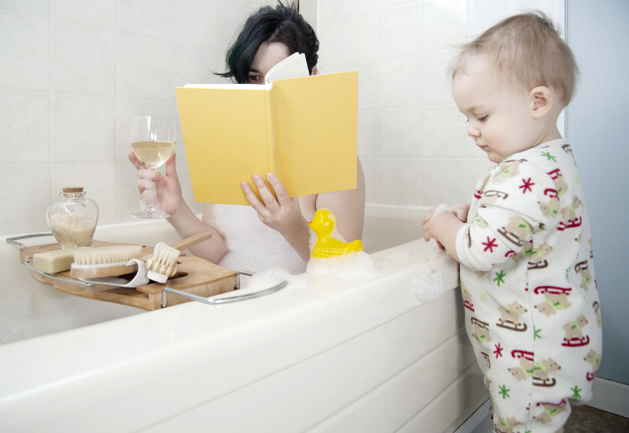 Mother in bathtub with glass of wine relaxing and toddler standing beside tub playing with toy