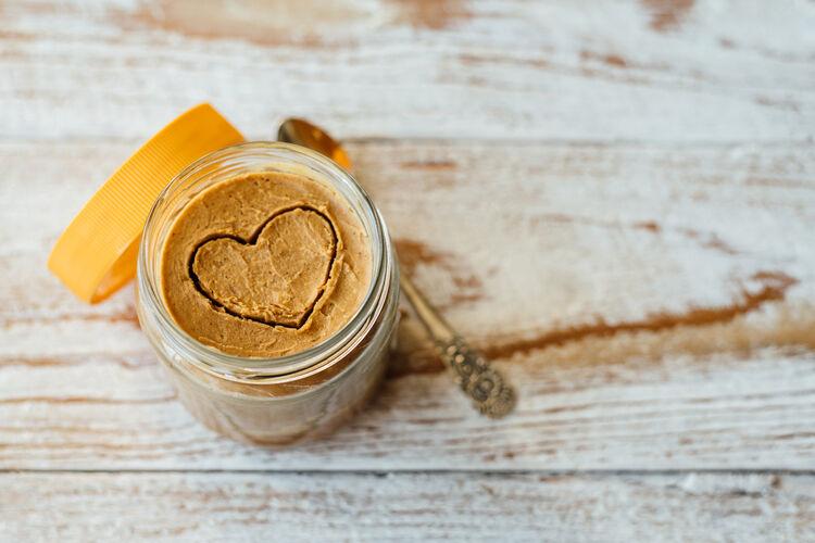 Heart drawn on peanut butter in glass jar