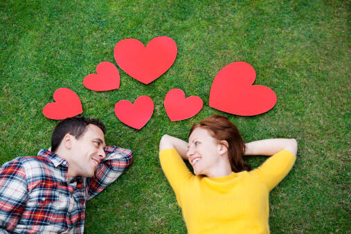 Couple laying in grass,surrounded by hearts.