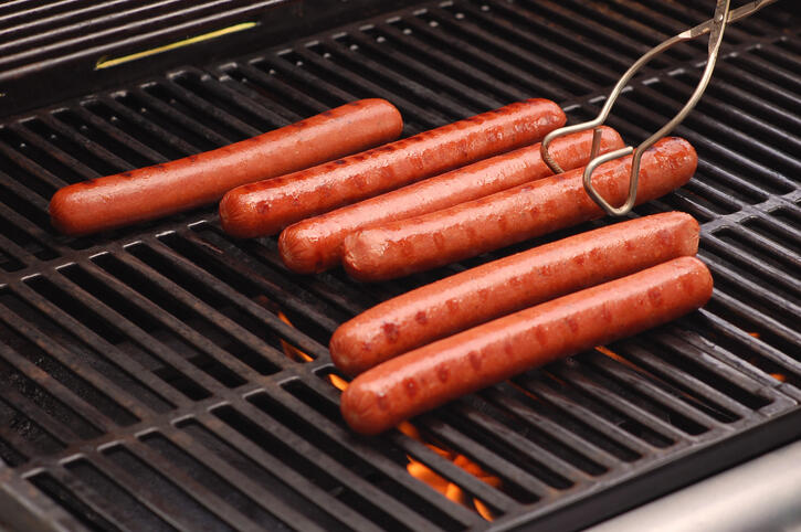 Six hot dogs cooking on a gas-fired barbeque grill. Flames licking the bottoms of the polish dogs are visible below the grill's grates.