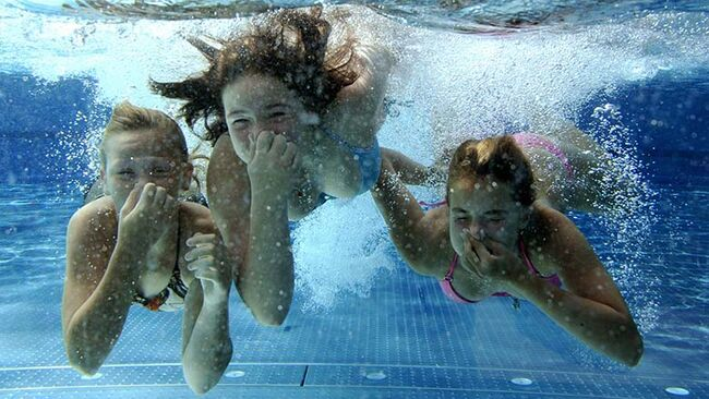 Three girls dive in a swimming pool on A