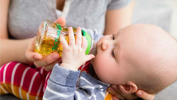 Mother feeding baby son with bottle
