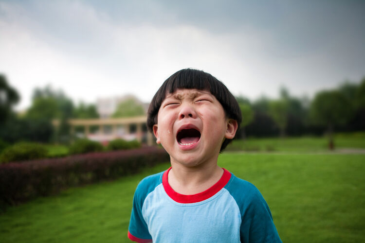 Little boy crying on grass