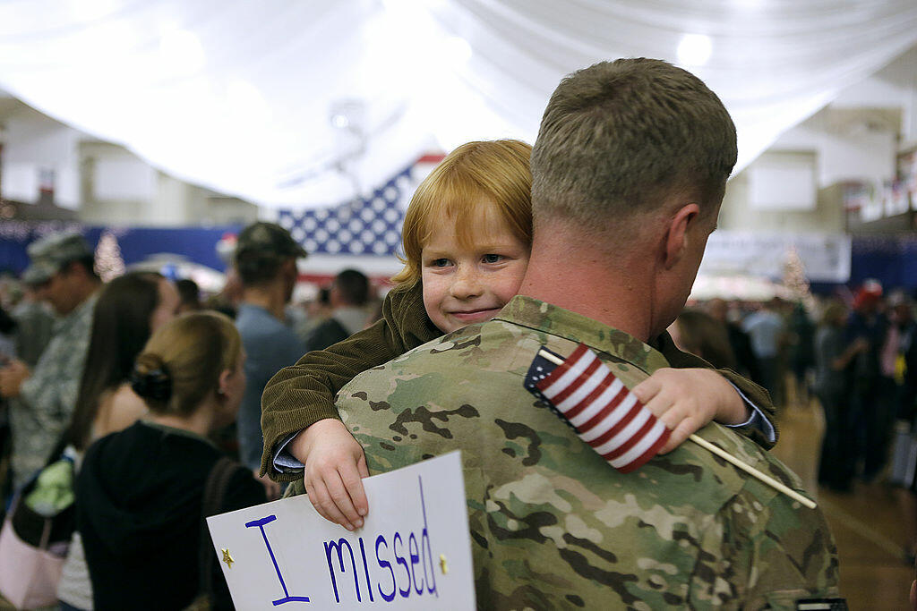 FORT CARSON, CO - NOVEMBER 4: Gavin Shaw, 5, flashes a smile as he hugs his father, Master Sergeant Adam Shaw, during a Welcome Home Ceremony for approximately 230 4th Brigade Combat Team soldiers, November 4, 2012 in Fort Carson, Colorado. The soldiers h