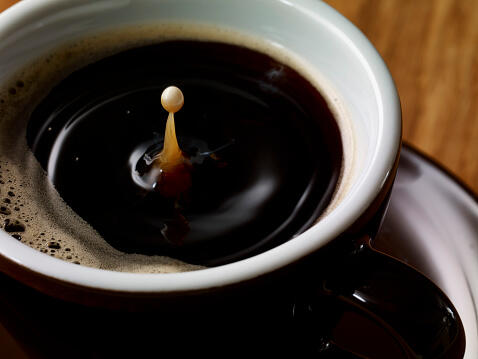 Drop of milk in cup of coffee
