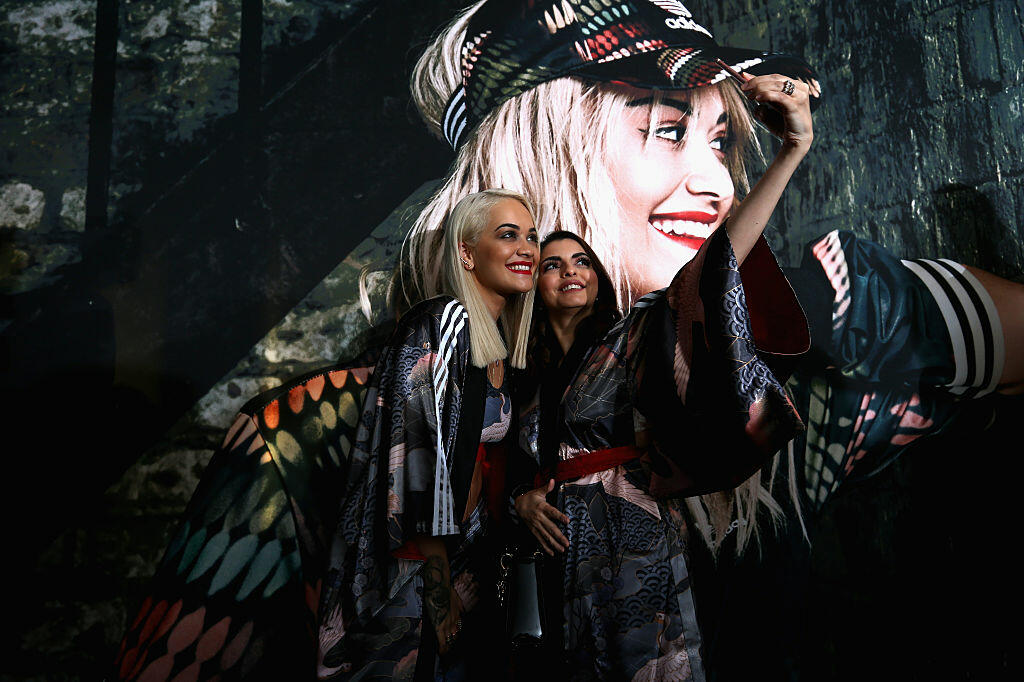 DUBAI, UNITED ARAB EMIRATES - FEBRUARY 10:  Rita Ora poses for a picture with a fan as she launches her adidas Originals Rita Ora SS16 collection at the Originals store at Dubai Mall on February 10, 2016 in Dubai, United Arab Emirates.  (Photo by Warren Little/Getty Images)