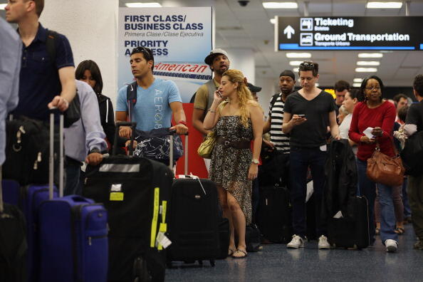 MIAMI, FL - APRIL 16:   American Airlines passengers wait in line for a flight at Miami International Airport on April 16, 2013 in Miami, Florida. Thousands of American Airlines travelers became stranded today when the airline was forced to ground all its