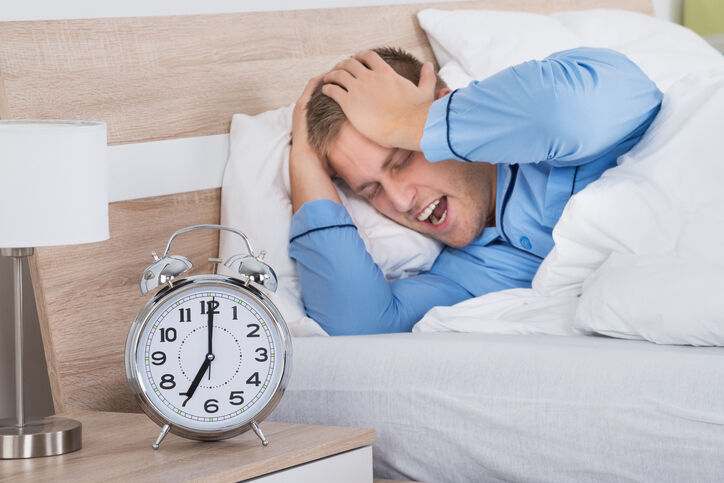 Sleeping Man Disturbed By Ringing Alarm Clock