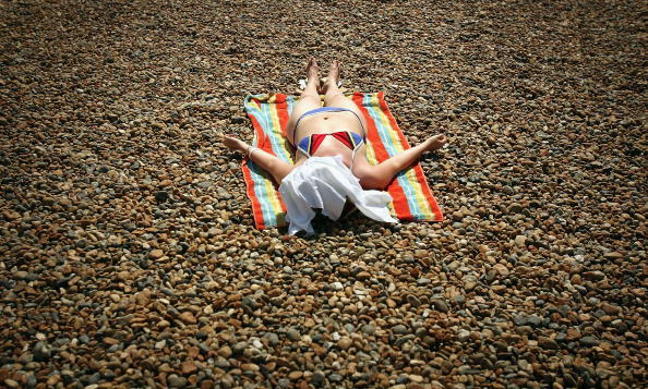BRIGHTON, UNITED KINGDOM - JUNE 19:  A woman sleeps in the sun on Brighton Beach, June 19, 2005 in Brighton, England.  Temperatures are likely to soar to 33C (91F) in London with similar highs in the south east.  (Photo by Bruno Vincent/Getty Images)