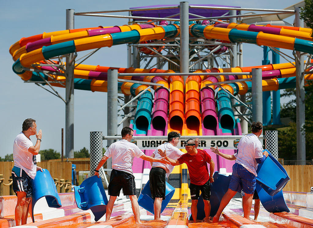 ARLINGTON, TX - MAY 20:  (2nd from R) IndyCar driver and defending Indy 500 champion Tony Kanaan reacts after riding on the new Wahoo Racer water slide with a group of local dignitaries at Hurricane Harbor on May 20, 2014 in Arlington, Texas.  (Photo by T