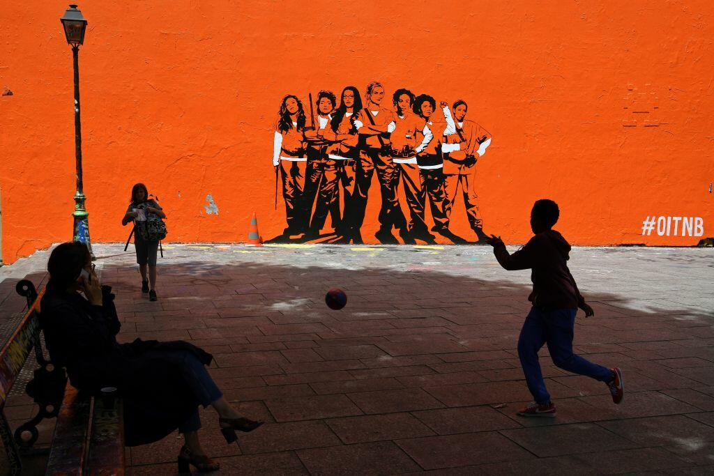 A boy plays football by a mural painting depicting the upcoming US series