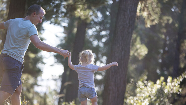 Father and daughter playing in the forest