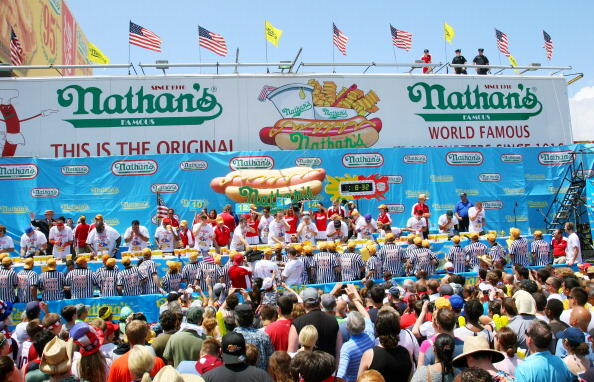 NEW YORK, NY- JULY 04:  People watch the Nathan's Famous Fourth of July Hot Dog Eating Contest at Nathan's Famous in Coney Island on July 4, 2013 in the Brooklyn borough of New York City. Chestnut, of San Jose, California, ate 69 hotdogs in ten minutes to