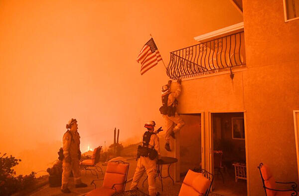 Firefighters save a US flag as impending flames from the Wall fire close in on a luxury home in Oroville, California on July 8, 2017. At least 10 structures have burned and the fire is currently at 20 percent containment. The first major wildfires after t