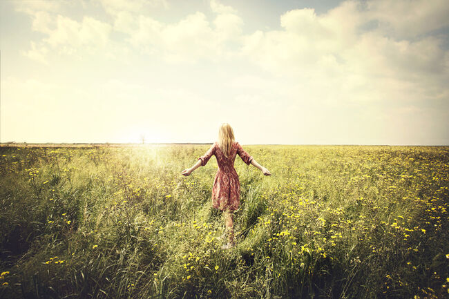dreamy woman walking in nature towards the sun