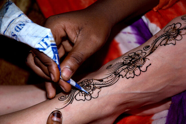 Cropped Image Of Artist Applying Henna Tattoo On Woman Leg