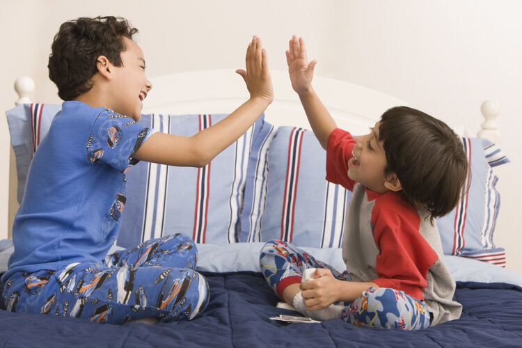 Hispanic brothers high fiving on bed