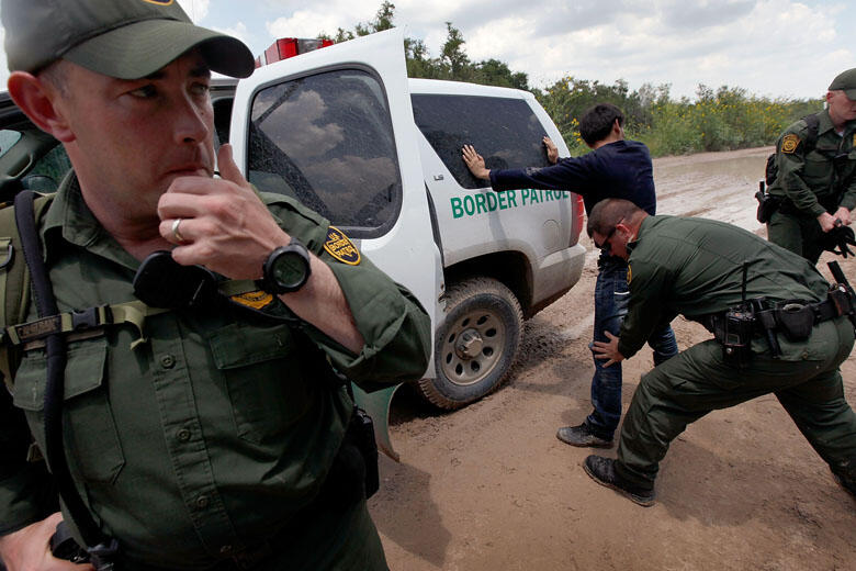 MCALLEN, TX - MAY 27:  A Border Patrol agent searches an undocumented immigrant apprehended near the Mexican border on May 27, 2010 near McAllen, Texas. The man was captured with several other immigrants including two young children in thick brush after c