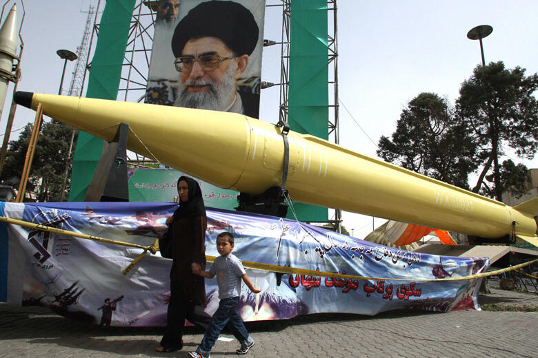 An Iranian woman and her son walk past S