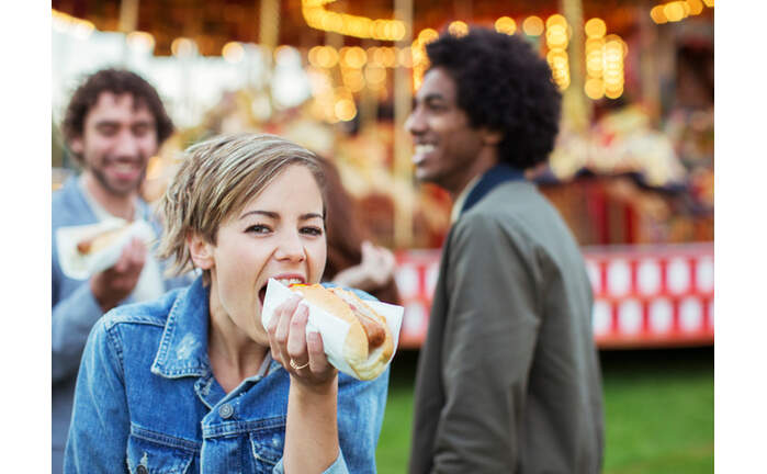 Three young people eating hot-dogs in amusement park