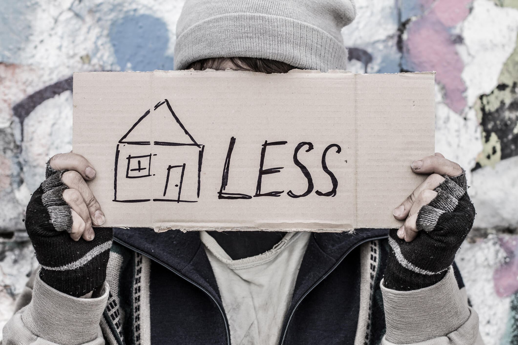 Young homeless man holding cardboard with painted house.