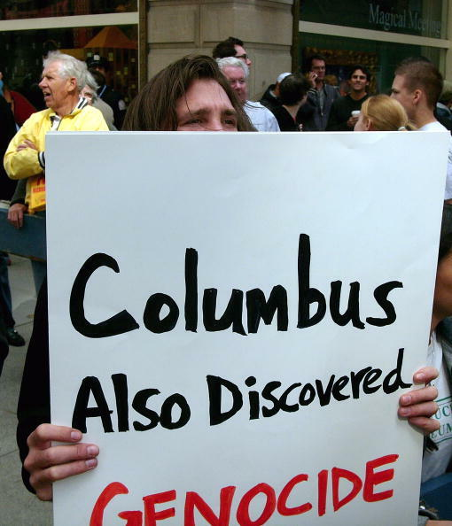 NEW YORK - OCTOBER 11: A man holds up an anti-Columbus sign during the Columbus Day Parade October 11, 2004, in New York City. The parade, which celebrates Italian heritage and Christopher Columbus' landing in America, featured historic race cars and sports cars. (Photo by Spencer Platt/Getty Images)