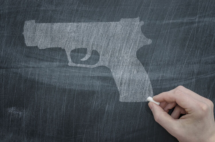 Gun on Chalkboard Getty Images