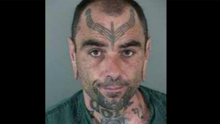 """FBI Searching For Fugitive With """"Dork"""" Tattooed Across His Neck"""