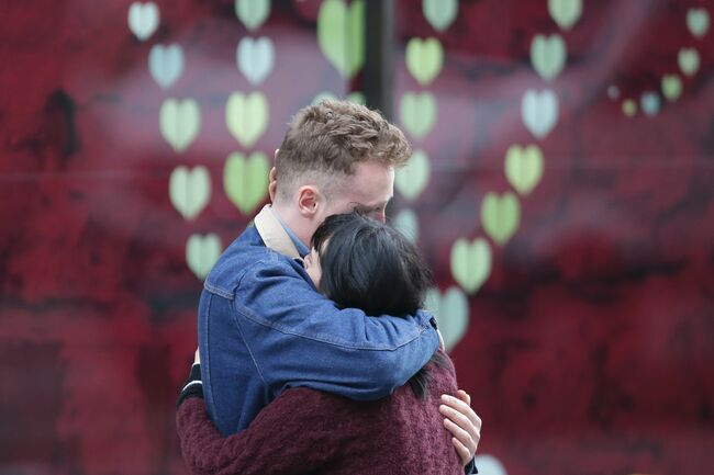 A couple hug at the police corden at the north end of London Bridge in London on June 4, 2017, after leaving a bunch of flowers in tribute to the victims of the June 3 terror attack. Seven people were killed in a terror attack on Saturday by three assailants on London Bridge and in the bustling Borough Market nightlife district, the chief of London's police force said on Sunday. Photo credit: DANIEL LEAL-OLIVAS/AFP/Getty Images