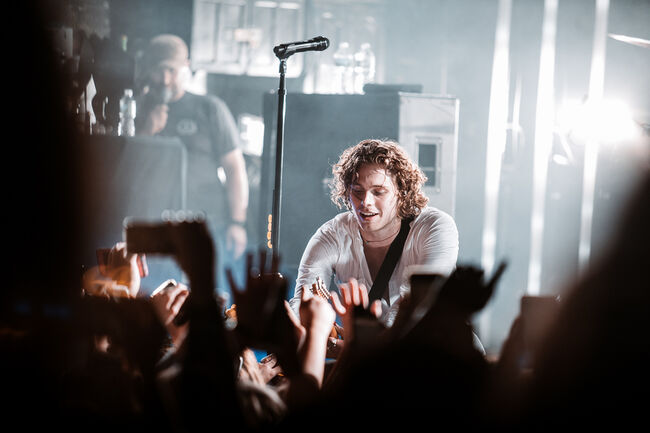 Luke Hemmings interacting with fans in the crowd at the intimate show