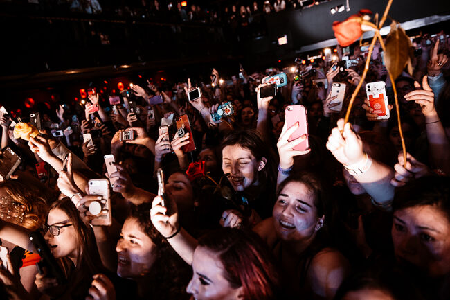 Fans holding their phones up as they sing along